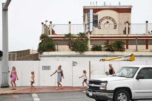 Pedestrians walk near blockades by the hurricane-damaged Flagship Hotel, June 8, 2010, in Galveston. The hotel was demolished in February 2011. Photo: Michael Paulsen, Houston Chronicle / Houston Chronicle