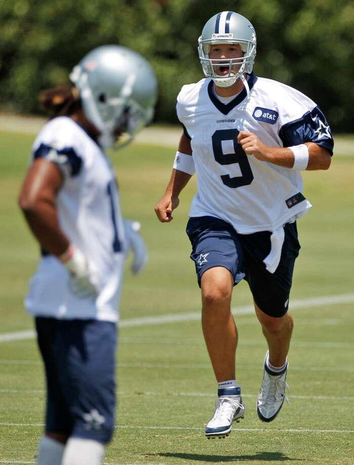 Cowboys cornerback Mike Jenkins did not attend organized team activities, but quarterback Tony Romo showed up Wednesday and ran sprints. Tony Gutierrez / Associated Press Photo: AP