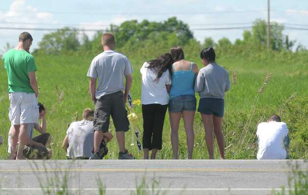 People gather near a cross erected at the scene of a fatal vehicle accident on Wednesday, May 23, 2012, in Halfmoon, NY.  Taylor  Mosher, 19, died when her vehicle crossed the line on Route 146 and struck an oncoming vehicle Tuesday evening.  (Paul Buckowski / Times Union) Photo: Paul Buckowski