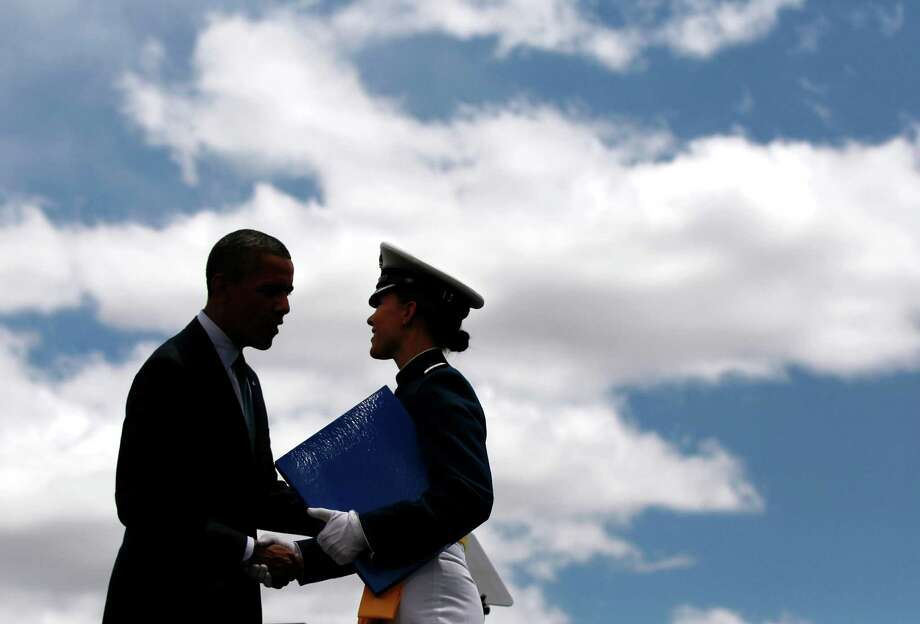 President Barack Obama is silhouetted as he congratulates a graduate of the 2012 Class of the U.S. Air Force Academy in Colorado Springs, Colo. Photo: Pablo Martinez Monsivais, Associated Press