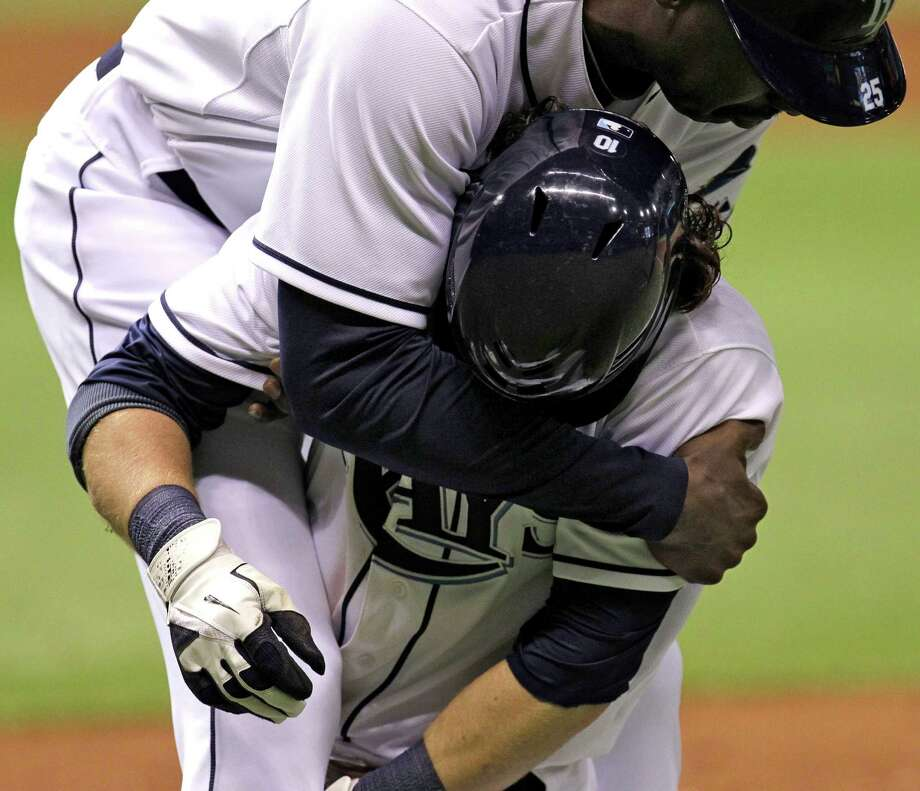Tampa Bay Rays first base coach George Hendrick (25) holds Will Rhymes after he collapsed at first base in the eighth inning during a baseball game against the Boston Red Sox on Wednesday, May 16, 2012, in St. Petersburg, Fla. Rhymes had been hit with a pitch by Boston's Franklin Morales. (AP Photo/Chris O'Meara) Photo: Chris O'Meara / AP