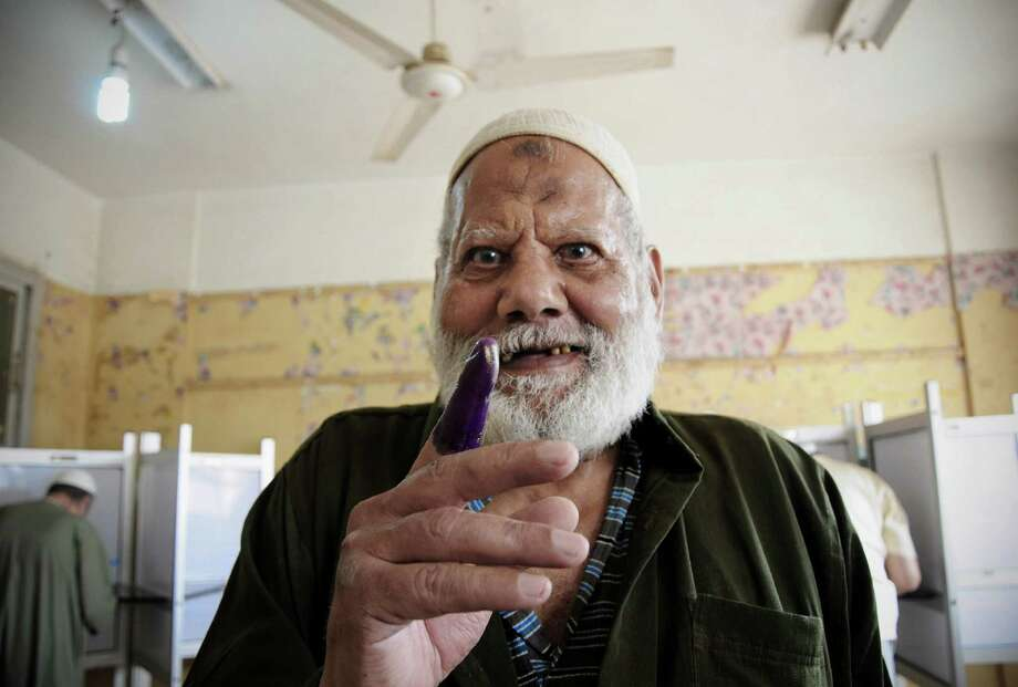 An Egyptian man shows his inked finger after casting his vote inside a polling station, in Giza, Egypt, Wednesday, May 23, 2012. More than 15 months after autocratic leader Hosni Mubarak's ouster, Egyptians streamed to polling stations Wednesday to freely choose a president for the first time in generations. (AP Photo/Mohammed Asad) Photo: Mohammed Asad / AP