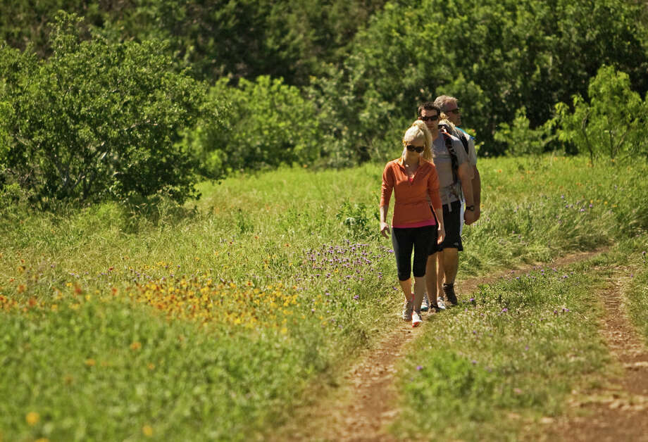 A group of hikers stroll among the wildflowers at Government Canyon State Natural Area, which will have moderate and more strenuous guided hikes during National Trails Day. Photo: JOHN GOODSPEED, SPECIAL TO THE EXPRESS-NEWS / SAN ANTONIO EXPRESS-NEWS