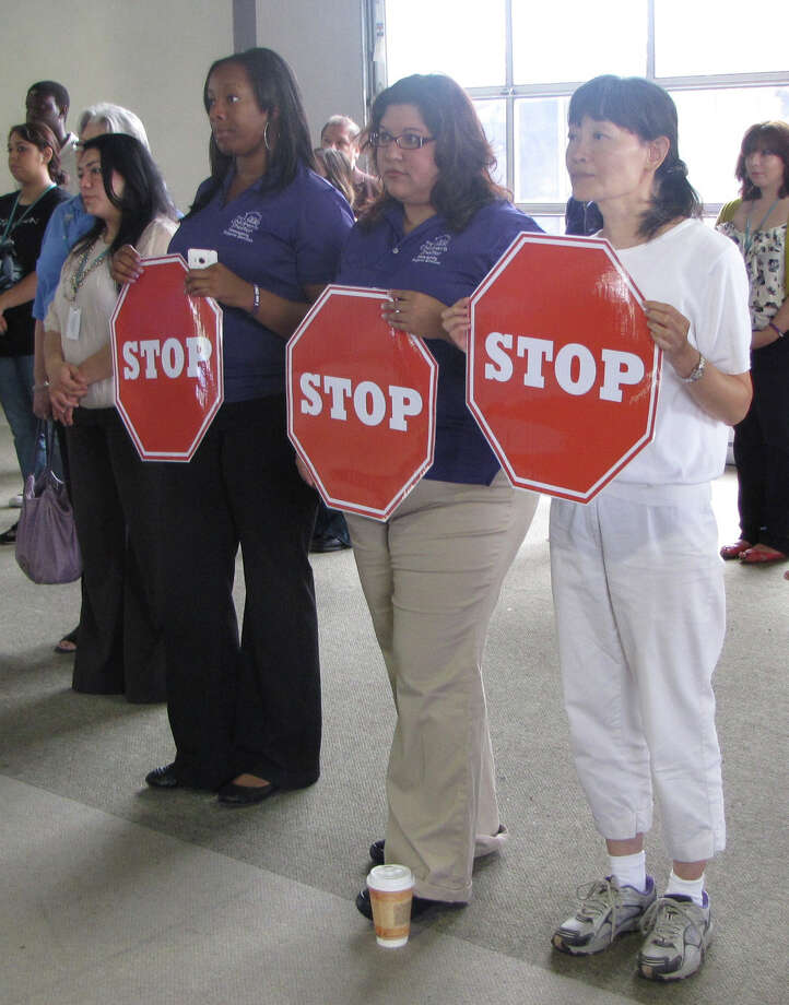 Attendees at a child abuse and neglect press conference hold up STOP signs at The Children's Shelter Wednesday morning. From left, in purple shirts, are The Children's Shelter employees Sharlene Holland, Nicole Barrera and Shujan Cheng, a prospective adoptive parent. Photo by Eva Ruth Moravec. Photo: EVA RUTH MORAVEC, San Antonio Express-News / emoravec@express-news.net