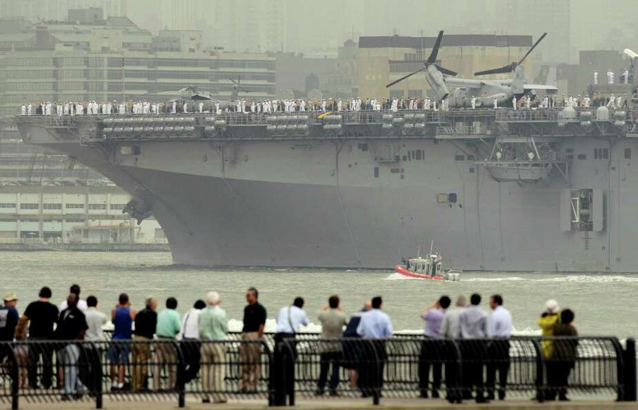 People watch the USS Wasp sail up the Hudson River from Jersey City, N.J., Wednesday, May 23, 2012.