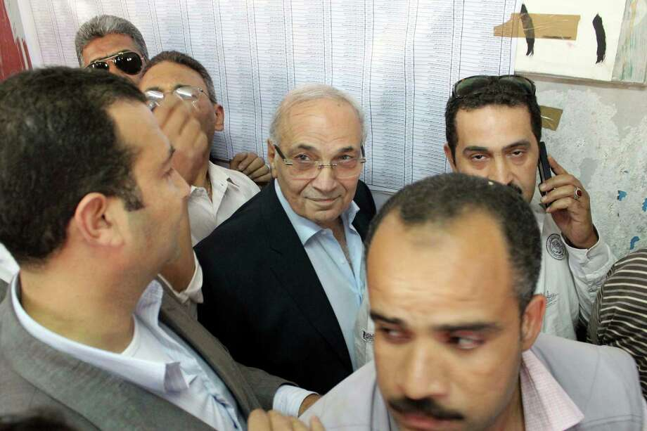 "Egyptian presidential candidate Ahmed Shafiq, center, arrives to vote at a polling site in Cairo, Egypt, Wednesday, May 23, 2012. Presidential Candidate and former Egyptian Prime Minister Ahmed Shafiq was met by scores of protesters as he arrived to cast his vote on Wednesday. Shafiq arrived to vote in an upscale neighborhood east of Cairo to protesters yelling ""down with the feloul"" or ""remnants"" of the regime. Photo: Anonymous, Associated Press / AP"