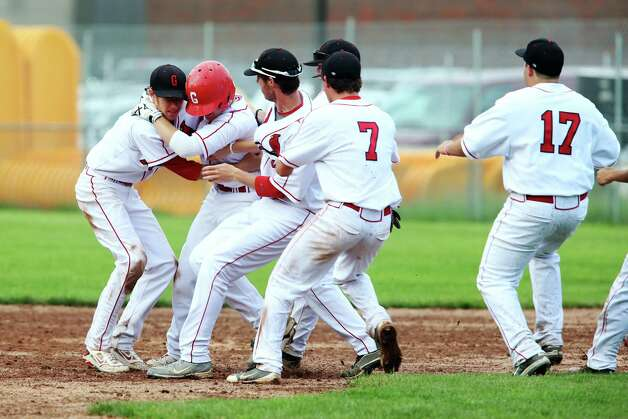 Greenwich High School's Matt Pruner (second from left) is congratulated by his teamates after scoring the winning run against Danbury in the FCIAC baseball quarterfinals on Wednesday May 23, 2012. Greenwich would keep their undefeated record for the season and advance to the finals. Photo: Mike Ross / Greenwich Time freelance