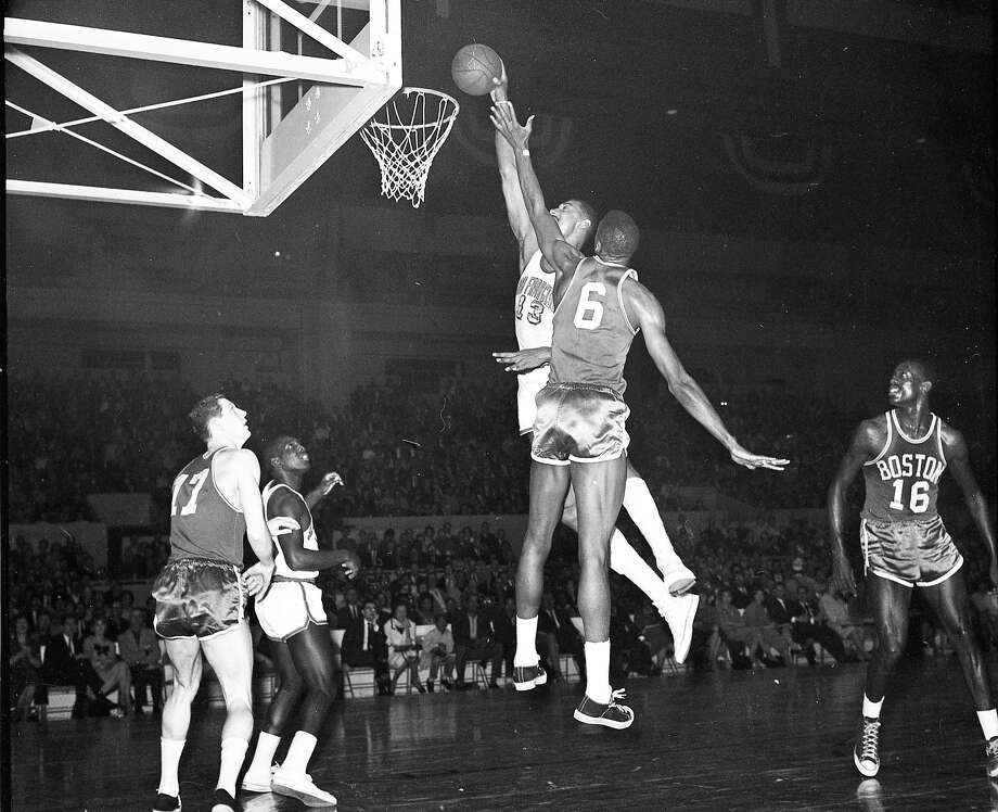 Wilt Chamberlain lays the ball in over Bill Russell during a game between the San Francisco Warriors and Boston Celtics. Feb. 21, 1963. At the Cow Palace. Photo: Joseph J. Rosenthal, The Chronicle