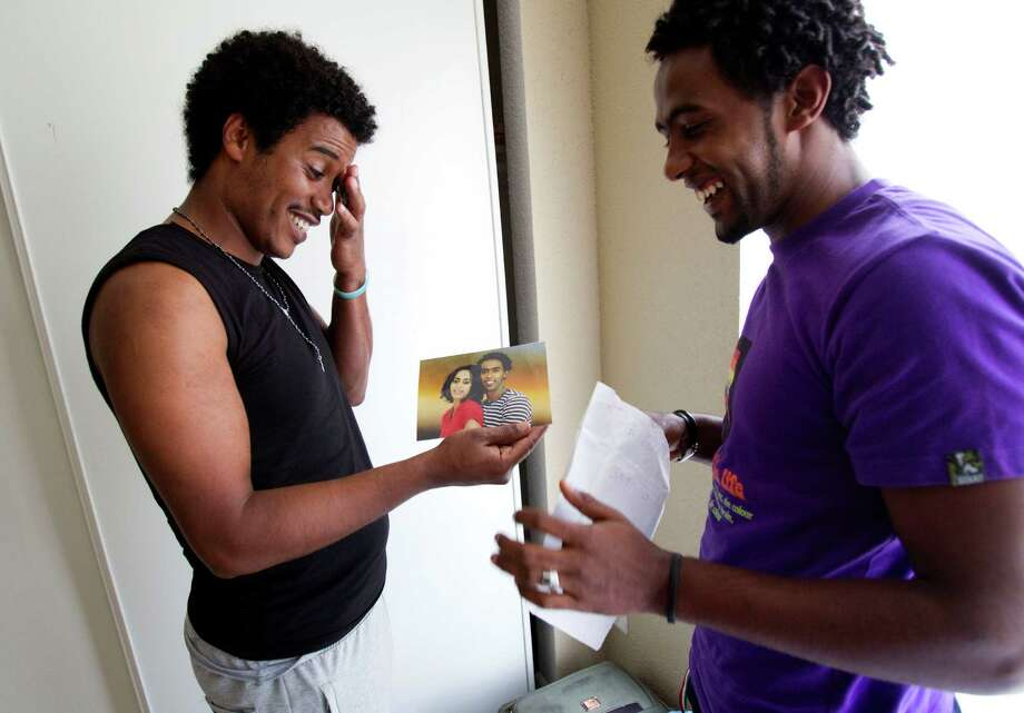 Refugees Isaias Tekle, left, and Yakob Tekie, share photos in their new apartment Wednesday, the day after being resettled in Houston. They hope to attend school. Photo: Brett Coomer / © 2012 Houston Chronicle