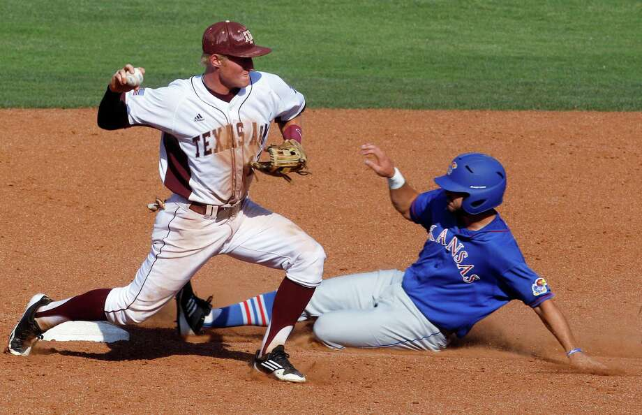Texas A&M second baseman Scott Arthur, left, forces out Kansas' Dakota Smith, right, on a fielder's choice hit by Jake Marasco in the seventh inning of a Big 12 conference tournament baseball game in Oklahoma City, Wednesday, May 23, 2012. Texas A&M won 10-4. (AP Photo/Sue Ogrocki) Photo: Sue Ogrocki, Associated Press / AP