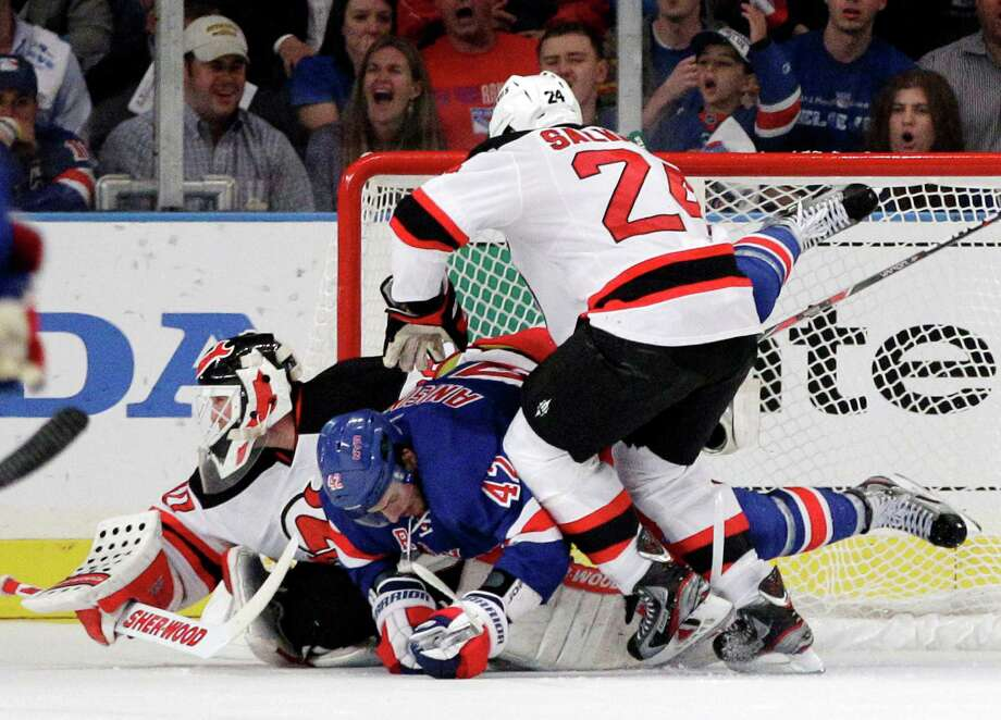 The Rangers' Artem Anisimov (center) finds himself in the middle of Devils goalie Martin Brodeur and teammate Bryce Salvador. Photo: AP