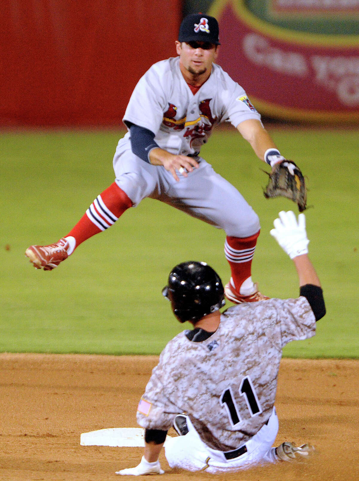 Springfield Cardinals shortstop Greg Garcia jumps to avoid Dean Anna of the San Antonio Missions as he turns a double play during Texas League baseball action at Wolff Stadium on Wednesday, May 23, 2012.