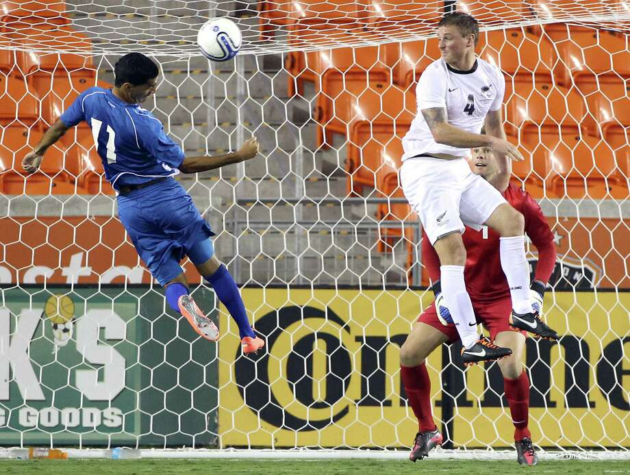 El Salvador's Ricardo Antonio Ulloa Alonzo, left, misses a header as New Zealand's Ben Sigmund (4) and Mark Paston watch during the second half of an international friendly game, Wednesday, May 23, 2012, in BBVA Compass Stadium in Houston. Photo: Nick De La Torre, Houston Chronicle / © 2012  Houston Chronicle