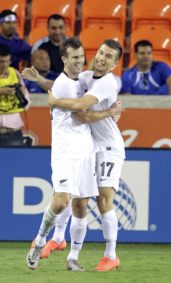 Ian Hogg, of New Zealand, left gets a hug from Kosta Barbarouses after he scored a goal during the 28th minute half of an international friendly game, Wednesday, May 23, 2012, in BBVA Compass Stadium in Houston. Photo: Nick De La Torre, Houston Chronicle / © 2012  Houston Chronicle