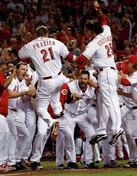 Cincinnati's Todd Frazier (21) jumps onto home plate after hitting a walk-off home run Wednesday. Photo: Al Behrman / AP