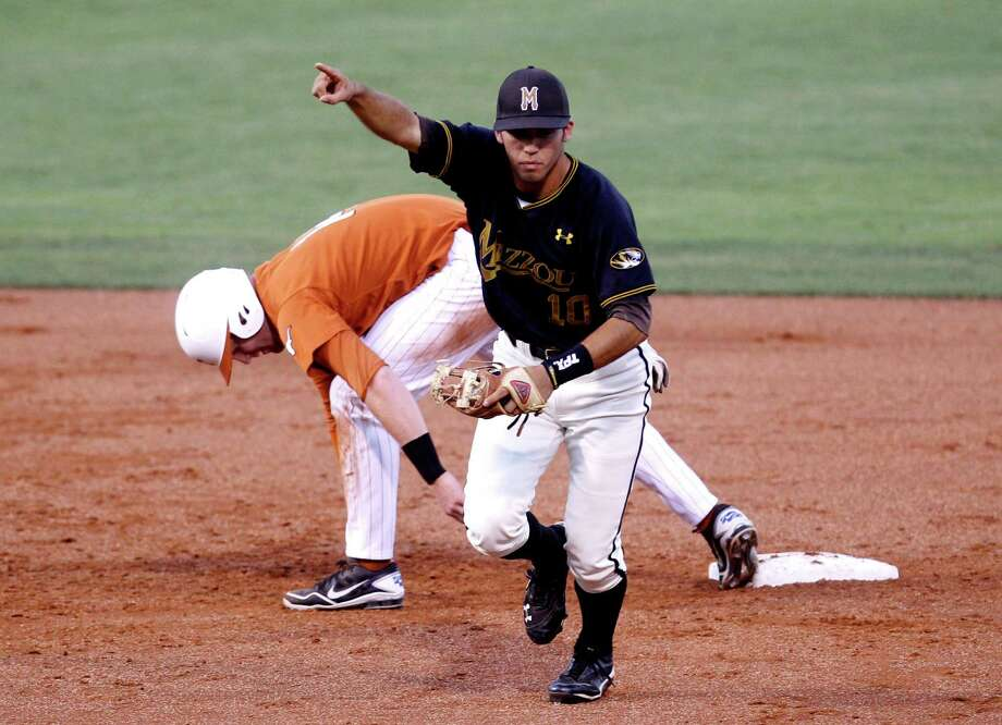 Missouri shortstop Eric Garcia (10) reacts after tagging out Texas' Kevin Lusson, left, on a pick-off in the third inning of a Big 12 conference tournament baseball game in Oklahoma City, Wednesday, May 23, 2012. (AP Photo/Sue Ogrocki) Photo: Sue Ogrocki, Associated Press / AP