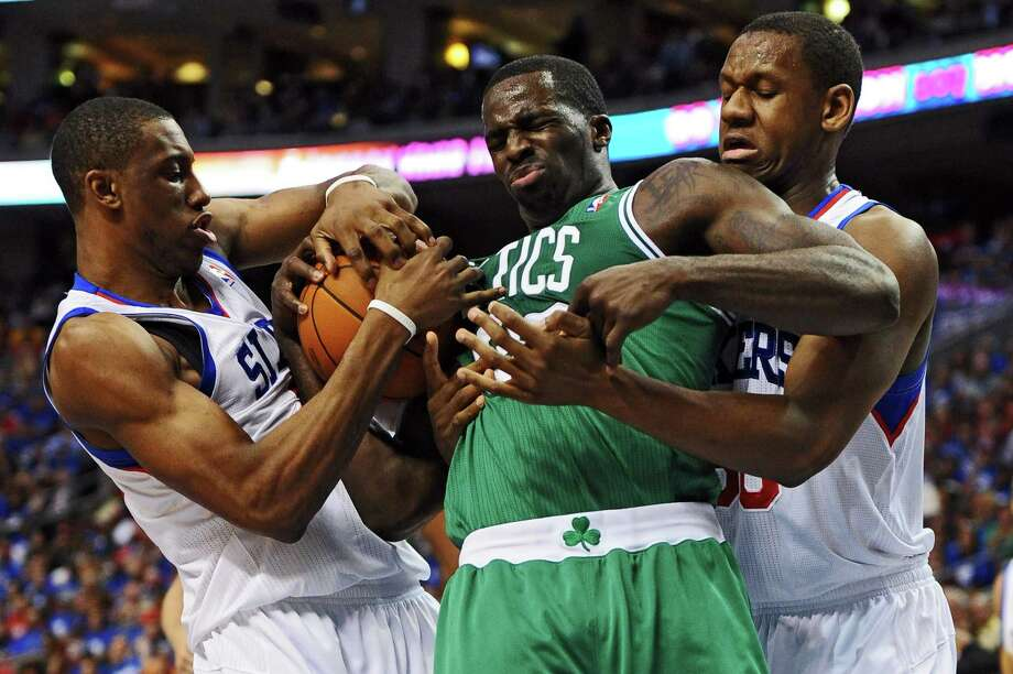After Brandon Bass, center, scored 27 points in the Celtics' Game 5 victory, he received extra attention from the likes of Thaddeus Young, left, and Lavoy Allen and was held to eight points on 2-of-12 shooting. Photo: Drew Hallowell / 2012 Getty Images