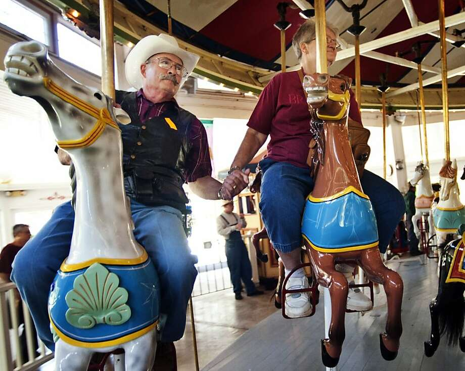 Ralph Coleman holds hands with his wife Nina while riding the 1912 Charles W. Parker Carousel in Crossroads Village in Genesee Township, Mich., on Wednesday, May 23, 2012. Hilda McShane, Genesee Parks' marketing specialist, estimated that 1,500-3,000 seniors came out to visit the 1800s-themed village. (AP Photo/The Flint Journal, Ryan Garza) Photo: Ryan Garza, Associated Press