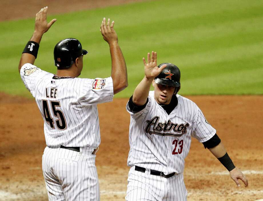 Carlos Lee, left, and Chris Johnson congregate at home after scoring on a fourth-inning triple by J.D. Martinez to put the Astros up for good. Photo: James Nielsen / © Houston Chronicle 2012