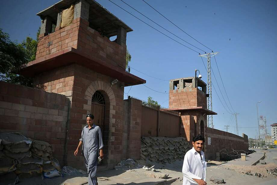 Pedestrians walk past the Peshawar central jail where Pakistani surgeon Shakeel Afridi, who worked for US intelligence, was moved after the verdict by tribal justice system of Khyber district, part of Pakistan's semi-autonomous tribal belt, in Peshawar on May 23, 2012.  Afridi, recruited by the CIA to help find Osama bin Laden, on May 23 was sentenced to 33 years in prison for treason, officials said.  In January, US Defense Secretary Leon Panetta confirmed Afridi had worked for US intelligence by collecting DNA to verify bin Laden's presence and expressed concern about Pakistan's treatment of him.   AFP PHOTO / A. MAJEEDA. MAJEED/AFP/GettyImages Photo: A. Majeed, AFP/Getty Images