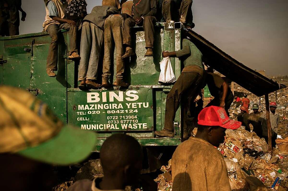Pickers hang out on a city waste bin inside Dandora dump.