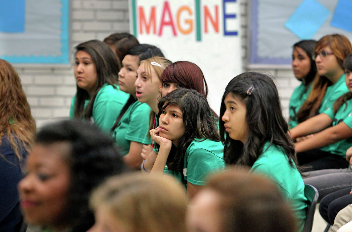 Mykayla Amador (center) from Brentwood Middle School listens as Rose González Pérez, CEO of the Girl Scouts of Southwest Texas, explains how the center will help girls and families. Wednesday, May 23, 2012.