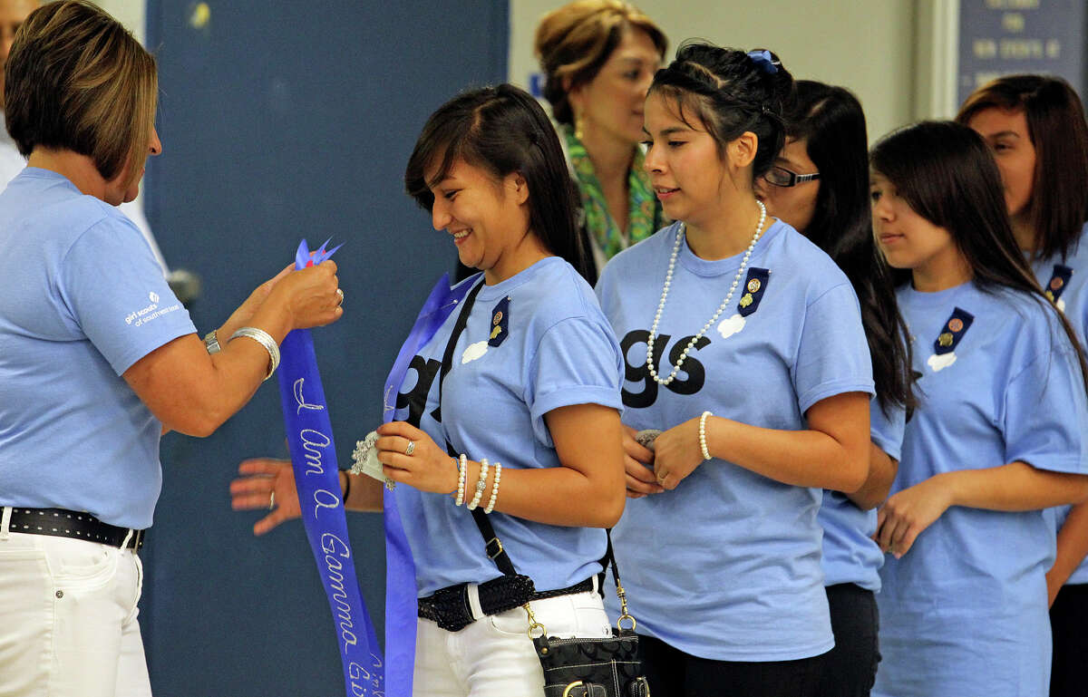 Melisa Bombella pins Gamma Girl ribbons on Girl Scouts as the Southwest Texas council and Edgewood ISD combine to start a center at the former Coronado/Escobar school campus on Wednesday, May 23, 2012.