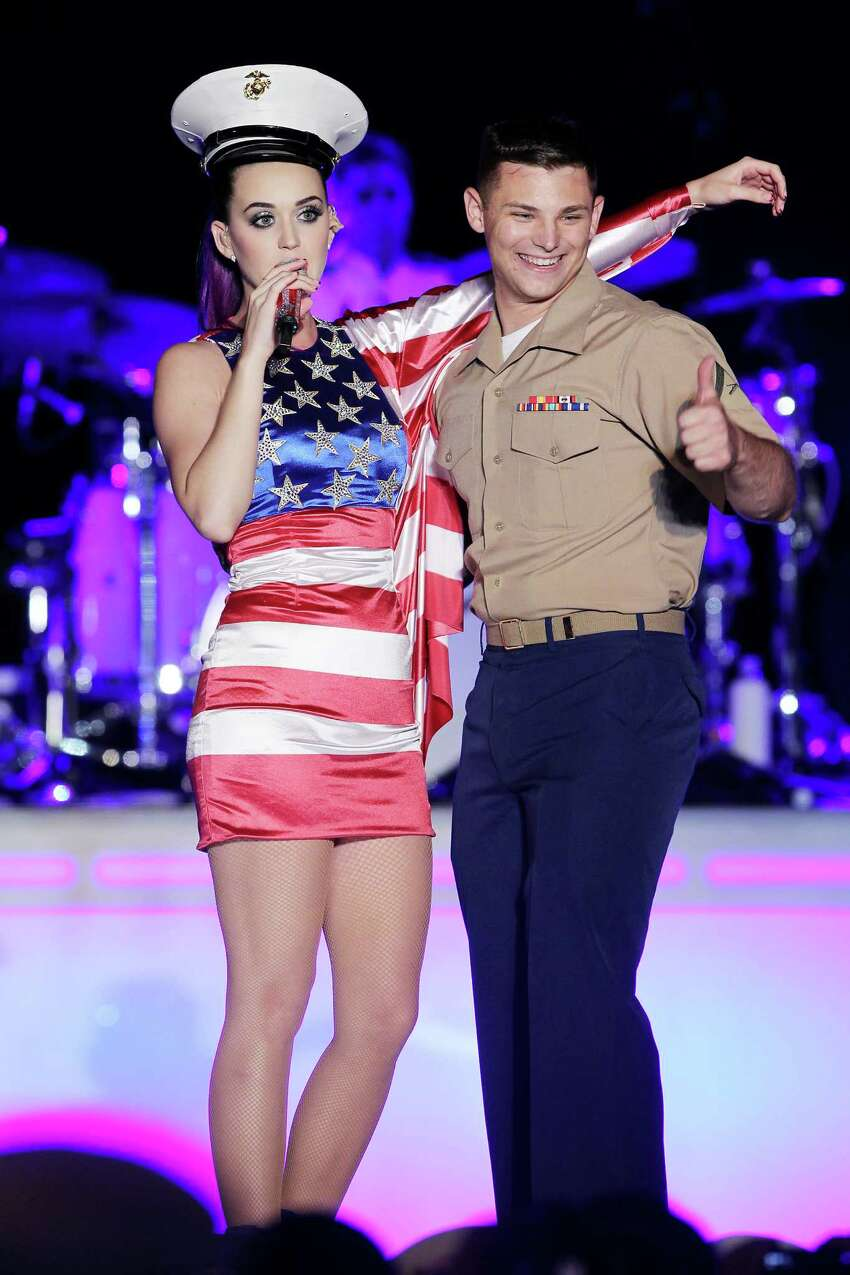 In this May 23, 2012 photo released by Starpix, singer Katy Perry stands with an unidentified U.S. Navy personnel as she performs at a Pepsi-sponsored event at Brooklyn Pier 9A, kicking off Fleet Week in New York. (AP Photo/Starpix, Amanda Schwab)