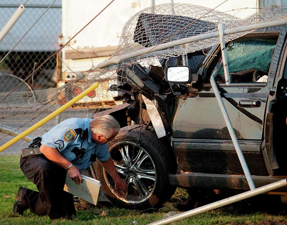 An HPD Vehicle Crimes Division Officer inspects the wheels on a crashed SUV along the service road of 610 South Loop near Calais Road on Thursday, May 24, 2012. The SUV's driver died in the collision with a parked trailer. Photo: Mayra Beltran, Houston Chronicle / Houston Chronicle