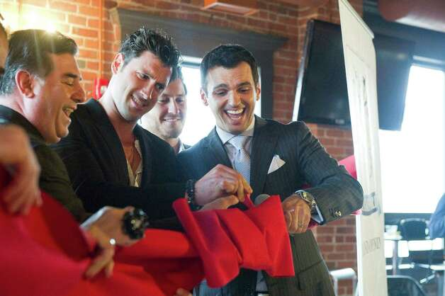 "Stamford Mayor Michael Pavia helps brothers Maksim,  left, and Val Chmerkovskiy, center, and Tony Dovolani, dancers on ABC's reality competition ""Dancing With the Stars,"" cut the ribbon as they open Dance With Me Stamford, their fourth ballroom dance studio and their first in Connecticut, on Summer Street in Stamford, Conn., May 23, 2012. Photo: Keelin Daly / Stamford Advocate"