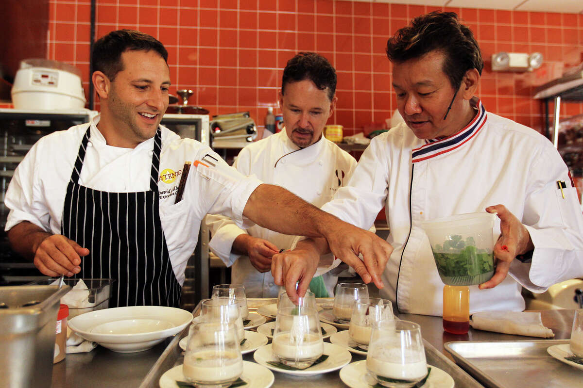 """Chef McDang plates his sour coconut and galangal soup with the help of Chef David Gilbert, left, and Chef Stephan Pyles, center, during his """"Principles of Thai Cookery"""" class at Sustenio, Saturday, May 19, 2012. (JENNIFER WHITNEY)"""