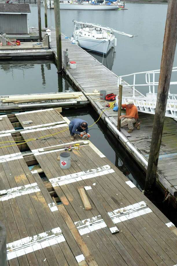 Carpenters Lan Phan, left, and Bill Delaney, right, work on making several small floating docks into one large dock at the Harbor Point boat yard on Thursday, May 24, 2012. Photo: Lindsay Niegelberg / Stamford Advocate