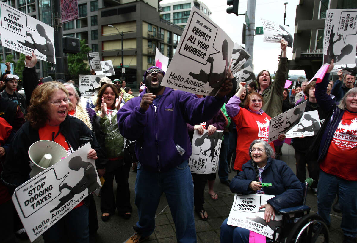 Darryl Johnson, center, and other protesters erupt after an announcement that Amazon pulled support for the American Legislative Exchange Council. The group gathered outside the Amazon shareholders meeting on Thursday, May 24, 2012 at the Seattle Art Museum. Protesters asked Amazon to pull support for the American Legislative Exchange Council, accused Amazon of poor working conditions for its warehouse workers and tax dodging.