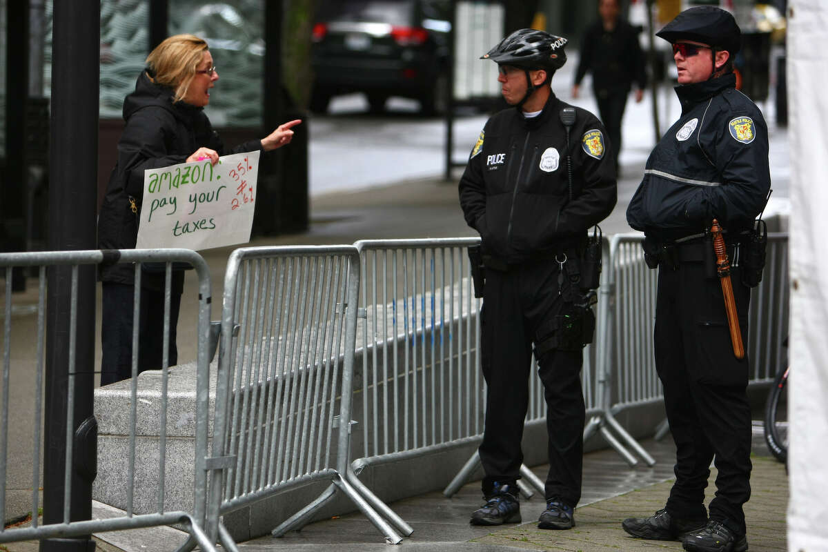 A protester speaks to police officer surrounding the Seattle Art Museum during the Amazon shareholders meeting. Protesters gathered outside the Amazon shareholders meeting asking Amazon to pull support for the American Legislative Exchange Council. They also accused Amazon of poor working conditions for its warehouse workers and tax dodging.