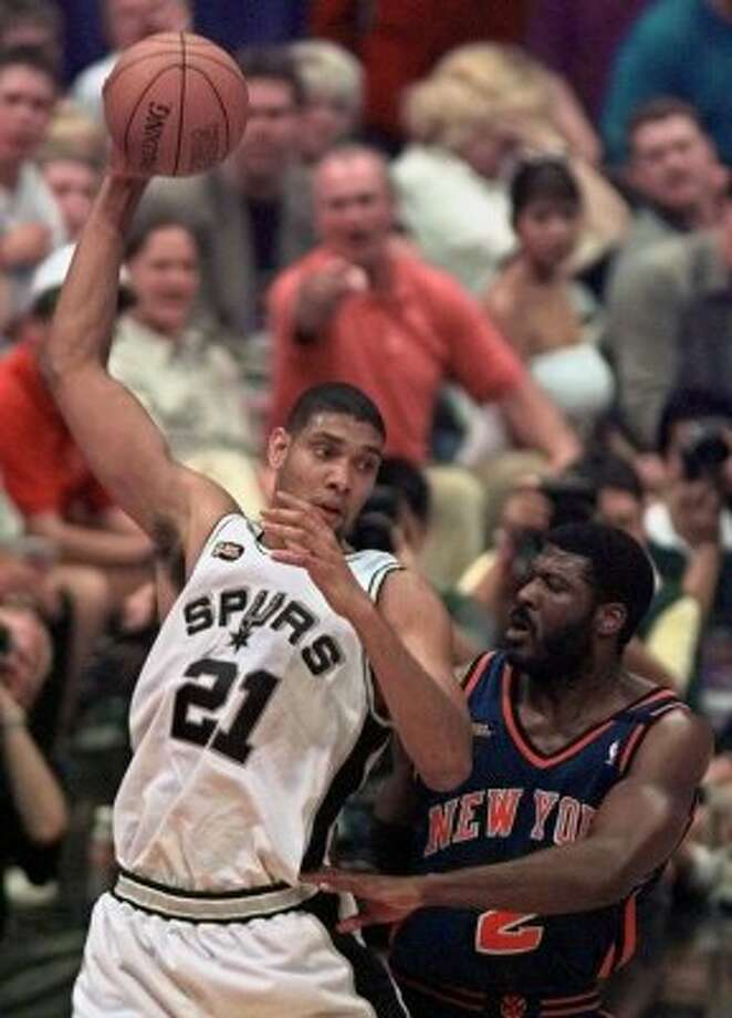 1999 starting power foward: San Antonio Spurs forward Tim Duncan, left, keeps the ball out of the reach of New York Knicks forward Larry Johnson, right, during Game 2 of the NBA finals in San Antonio, Texas, Friday, June 18, 1999. The Spurs defeated the Knicks 80-67. (AP)