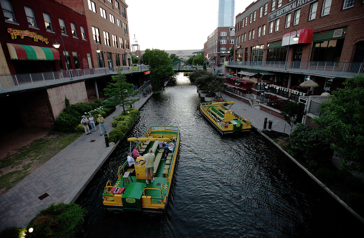 A water taxi boat takes visitors along the Bricktown Canal in Oklahoma City on Wednesday, May 23, 2012. The canal opened in 1999 and features a variety of restaurants, entertainment and culture. The canal is similar in concept to the San Antonio River Walk.