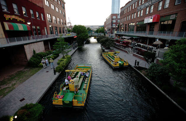A water taxi boat takes visitors along the Bricktown Canal in Oklahoma City on Wednesday, May 23, 2012. The canal opened in 1999 and features a variety of restaurants, entertainment and culture. The canal is similar in concept to the San Antonio River Walk. Photo: Kin Man Hui, San Antonio Express-News / ©2012 San Antonio Express-News