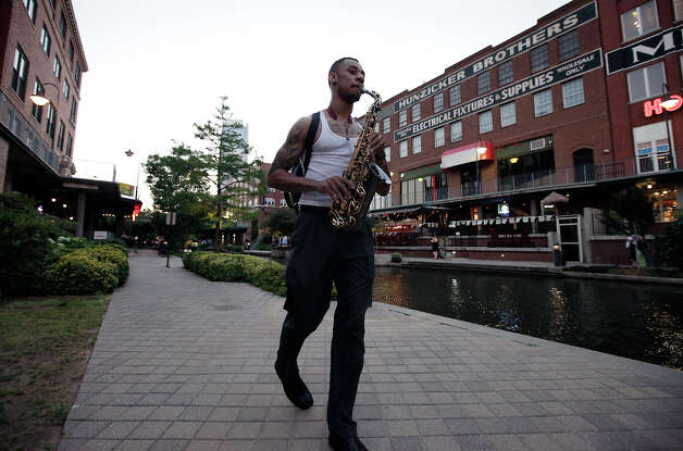 Saxophonist Rhyan Adams plays music while walking along the Bricktown Canal in Oklahoma City on Wednesday, May 23, 2012. The canal opened in 1999 and features a variety of restaurants, entertainment and culture. The canal shares many similar features to the San Antonio River Walk. Photo: Kin Man Hui, San Antonio Express-News / ©2012 San Antonio Express-News
