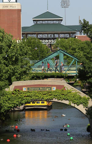 Visitors walk over a bridge at the Bricktown Canal in Oklahoma City on Wednesday, May 23, 2012. The canal opened in 1999 and features a variety of restaurants, entertainment and culture. The canal is similar in concept to the San Antonio River Walk. Photo: Kin Man Hui, San Antonio Express-News / ©2012 San Antonio Express-News