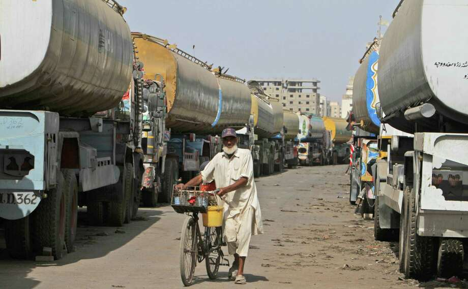 A Pakistani man selling cold drinks pushes his bicycle between oil tankers, which were used to transport NATO fuel supplies to Afghanistan, in a compound in Karachi, Pakistan, Thursday, May 24, 2012. (AP Photo/Fareed Khan) Photo: Fareed Khan / AP