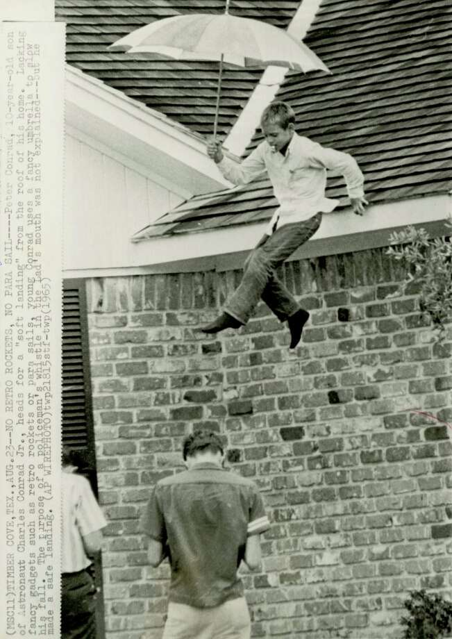 "NO RETRO ROCKETS, NO PARA SAIL-- Peter Conrad, 10-year-old son of astronaut Charles Conrad Jr., heads for a ""soft landing"" from the roof of his home. Lacking fancy gadgets such as retro rockets or para sails, young Conrad uses a fancy umbrella to slow his fall. The purpose of a policeman's whistle in the lad's mouth was not explained -- but he made a safe landing. (AP WIREPHOTO)(1965)"