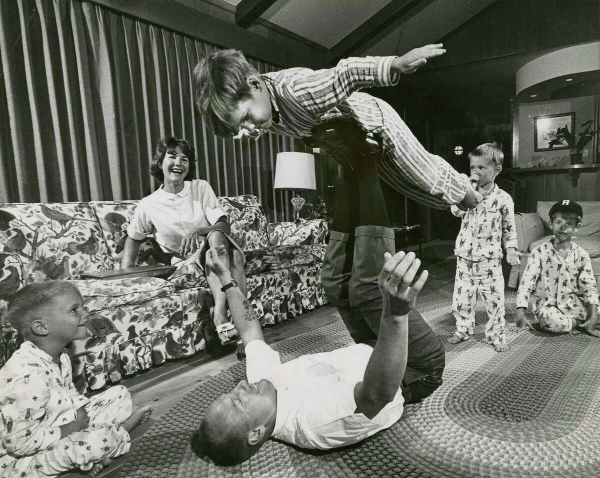 """June 1964: At home at Timber Cove, astronaut Charles (Pete) Conrad Jr. with his family. Flying on Dad's feet is Andy. In the photographer's note, the rest of the family is identified as, left to right, """"Thomas, Mom, Jane, Chris and Peter."""""""