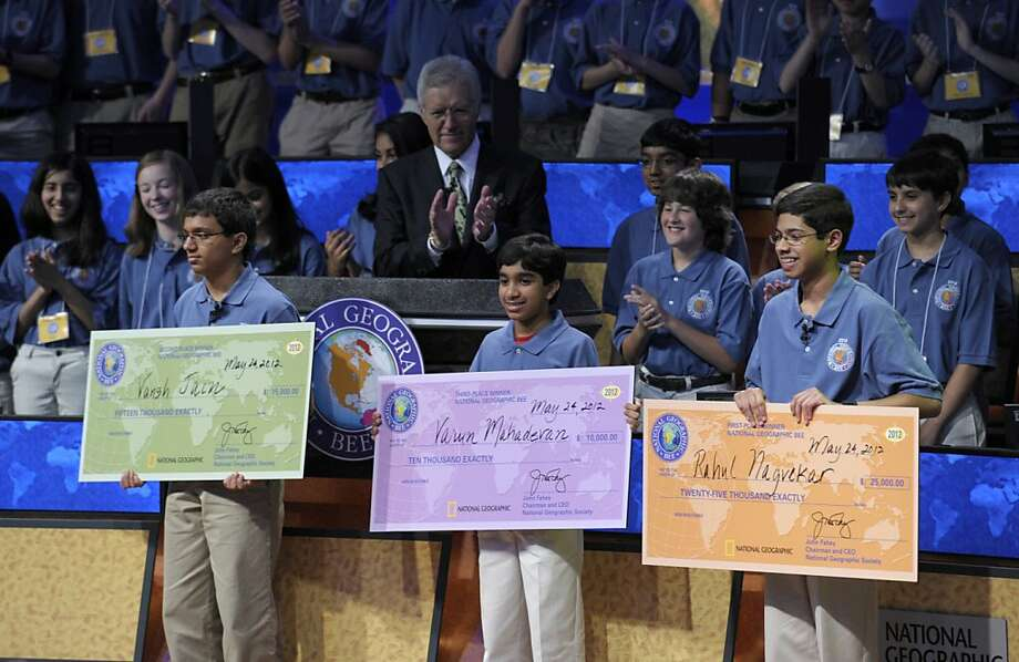 National Geographic Bee host Alex Trebek, rear center, and others, applaud the National Geographic Bee top winners, from left, Vansh Jain, from Minocqua-Hazel-hurst-Lake Tomahawk Elementary School in Minocqua, Wis.; Varun Mahadevan, from Prince of Peace Christian School in Fremont, Calif.; and champion Rahul Nagvekar, 14, from Quail Valley Middle School in Missouri City, Texas., Thursday, May 24, 2012, in Washington. (AP Photo/Susan Walsh) Photo: Susan Walsh, Associated Press