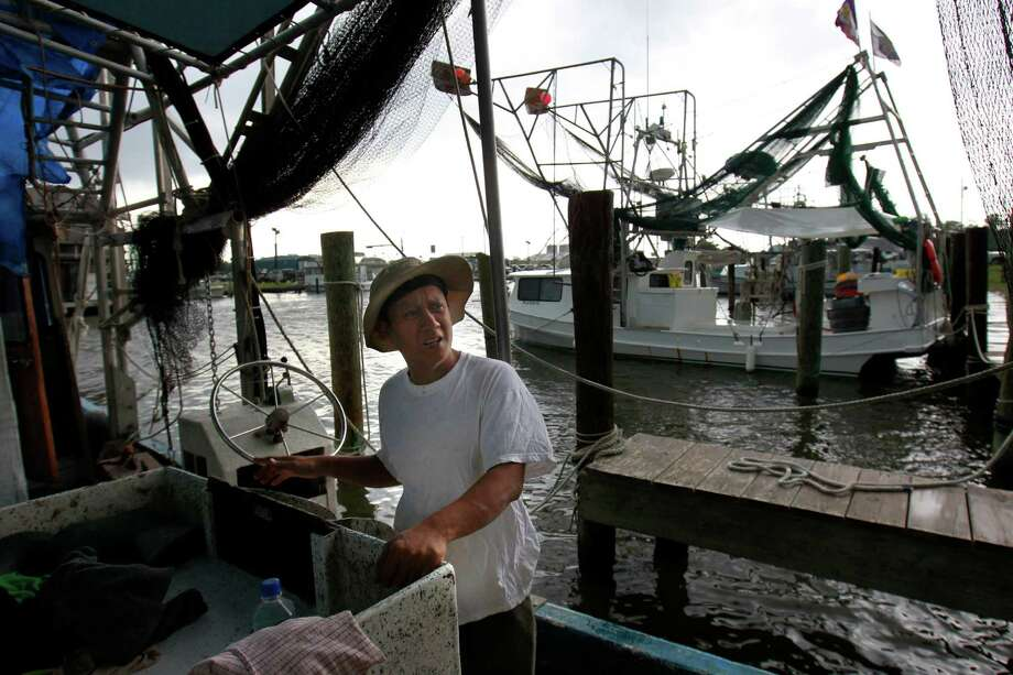 In this May 16, 2012, photo, Tuna Pham, a shrimper, talks as he works on his idle boat in Lafitte, La. The mood is gloomy on the hard-working shrimp and crab docks of this gritty fishing town in the Barataria estuary, a traditional seafood basket for New Orleans, as the second full year of fishing since BP's catastrophic oil spill kicks into high gear. Usually folks are upbeat and busy in May, the month when shrimpers get back to work in Louisiana's rich waters. But this spring, catches are down, docks are idle and anxiety is growing that the ill effects of the BP spill may be far from over. Photo: AP