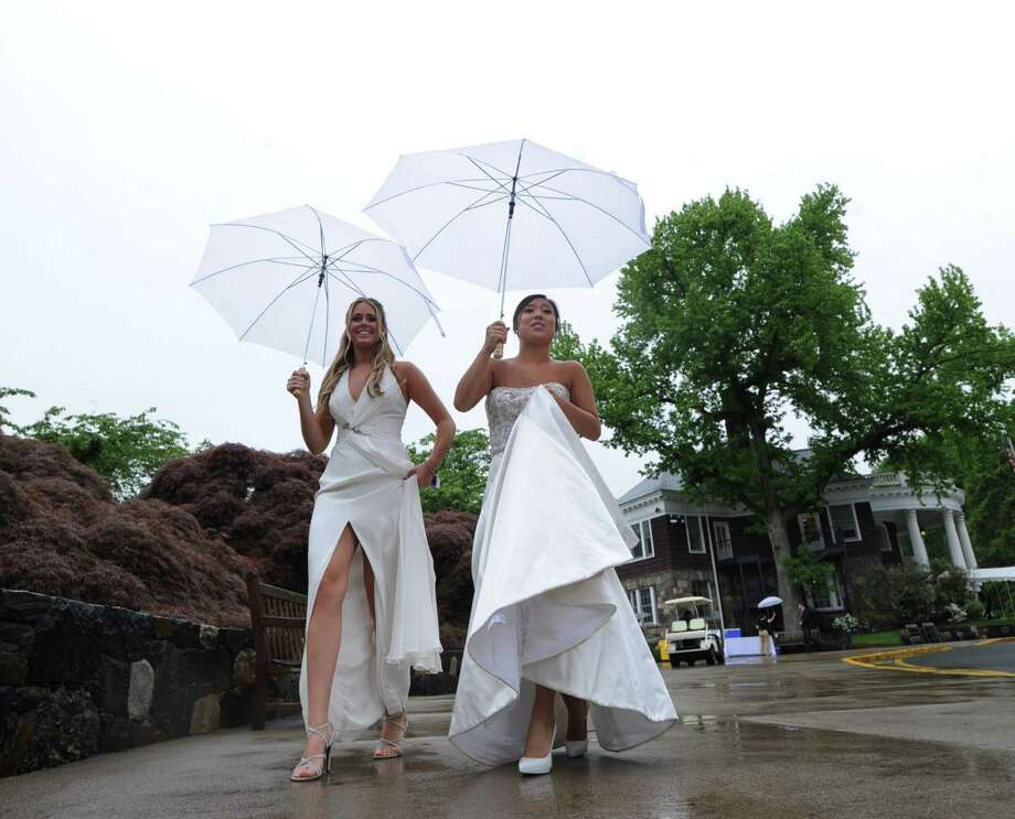 Greenwich Academy graduating seniors Nina Scott, left,  18, of Riverside, and Yuuka Sekiguchi, 18 of Greenwich, had the umbrellas out during the start of the Greenwich Academy Graduation at the main campus in Greenwich, Thursday, May 24, 2012. Photo: Bob Luckey / Greenwich Time