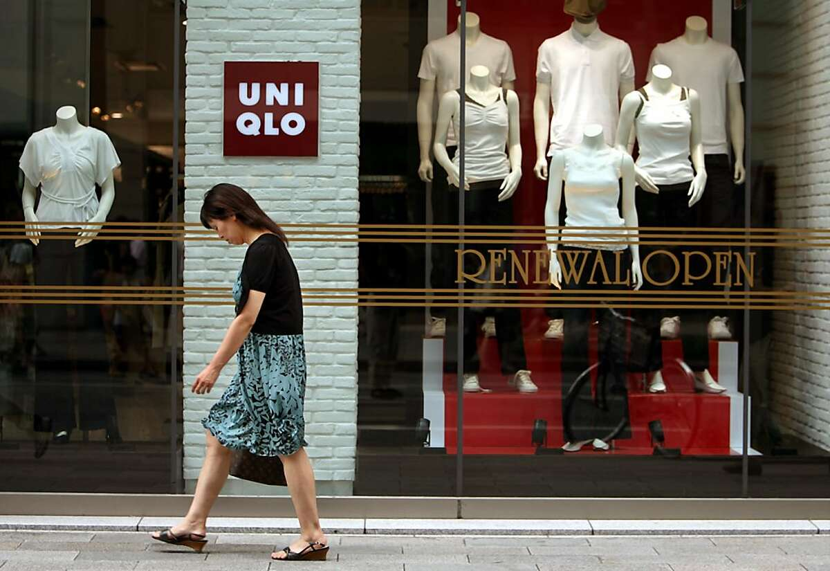 A pedestrian strolls in front of renewed Japanese apparel chain Uniqlo in a Ginza shopping district in Tokyo, Sunday, July 29, 2007. If you haven't yet heard of Uniqlo, chances are you will soon. Often called the Gap of Japan, the wildly popular apparel chain has taken its homeland by storm and is now turning its ambitions overseas. On Tuesday, Uniqlo's parent company, Fast Retailing, struck again with a brazen US$900 million takeover bid for upscale Barneys New York. (AP Photo/Junji Kurokawa)
