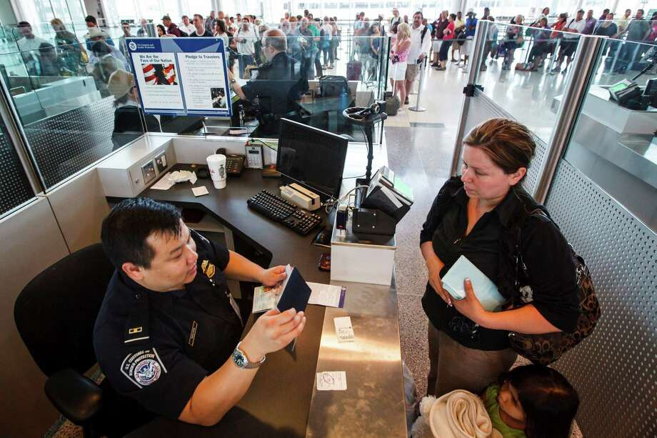 Dulce Hernandez, center, and her daughter, Magdalena Mendoza, 3, have their passports inspected by U.S. Customs and Border Protection officer Nguyen at the Federal Inspection Services customs facility at Bush Intercontinental Airport in Terminals E, Wednesday, May 23, 2012, in Houston. Photo: Michael Paulsen, Houston Chronicle / © 2012 Houston Chronicle