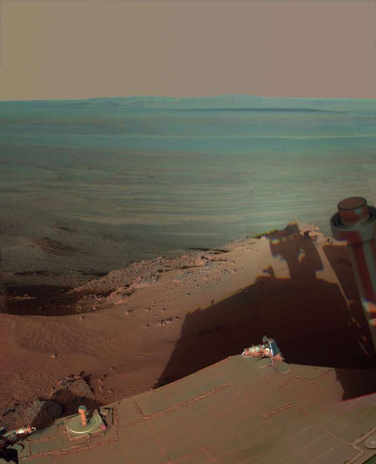 In this undated image provided by NASA, Mars Rover Opportunity catches its own late-afternoon shadow in a view eastward across Endeavour Crater on Mars. The rover used a panoramic camera between about 4:30 and 5:00 p.m. local Mars time to record images taken through different filters and combined into this mosaic view. Most of the component images were recorded during the 2,888th Martian day, or sol, of Opportunity's work on Mars, which corresponds to March 9, 2012 on Earth. The view is presented in false color to make some differences between materials easier to see, such as the dark sandy ripples and dunes on the crater's distant floor. Opportunity has been studying the western rim of Endeavour Crater since arriving there in August 2011. (AP Photo/NASA/JPL-Caltech/Cornell/Arizona State University) / NASA/JPL-Caltech/Cornell/Arizona