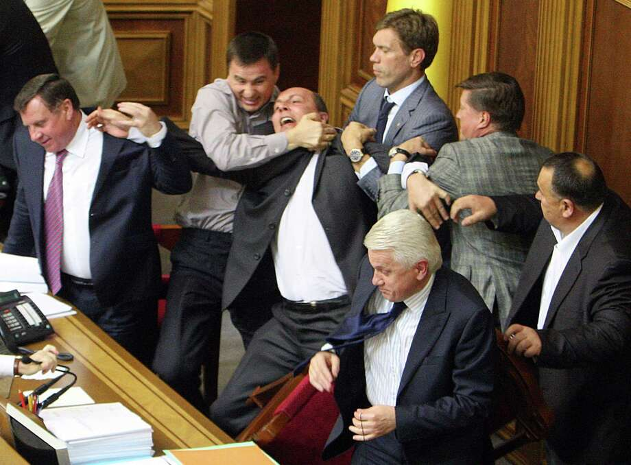Speaker of the Ukrainian parliament Volodymyr Litvin (Bottom) looks on as deputies of the Ukrainian opposition fight with deputies of the pro-presidential majority during a session of parliament in Kiev, as opposition parties protest a bill proposed by the ruling party which would make Russian an official state language along with Ukrainian. Photo: STR, AFP/Getty Images / AFP