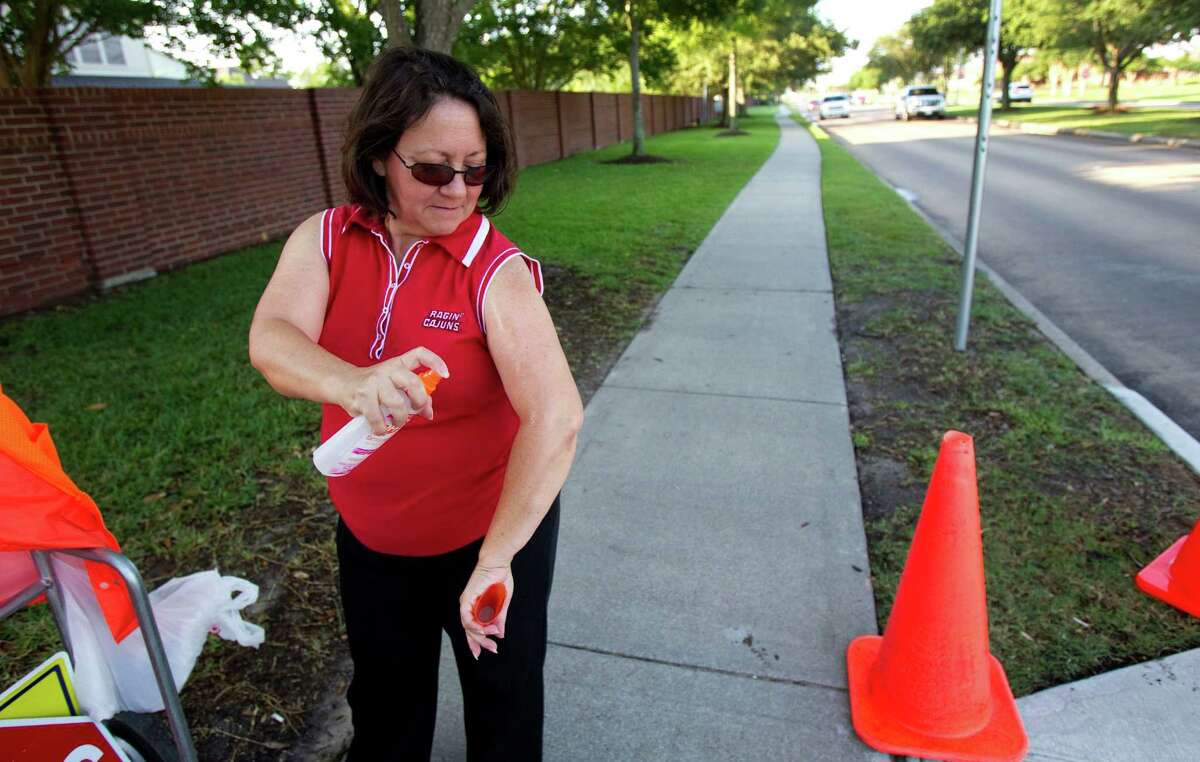 School crossing guard Angie Foret sprays her arms before her shift Wednesday in Pearland. Foret said mosquitoes have been a real problem at her crossing.